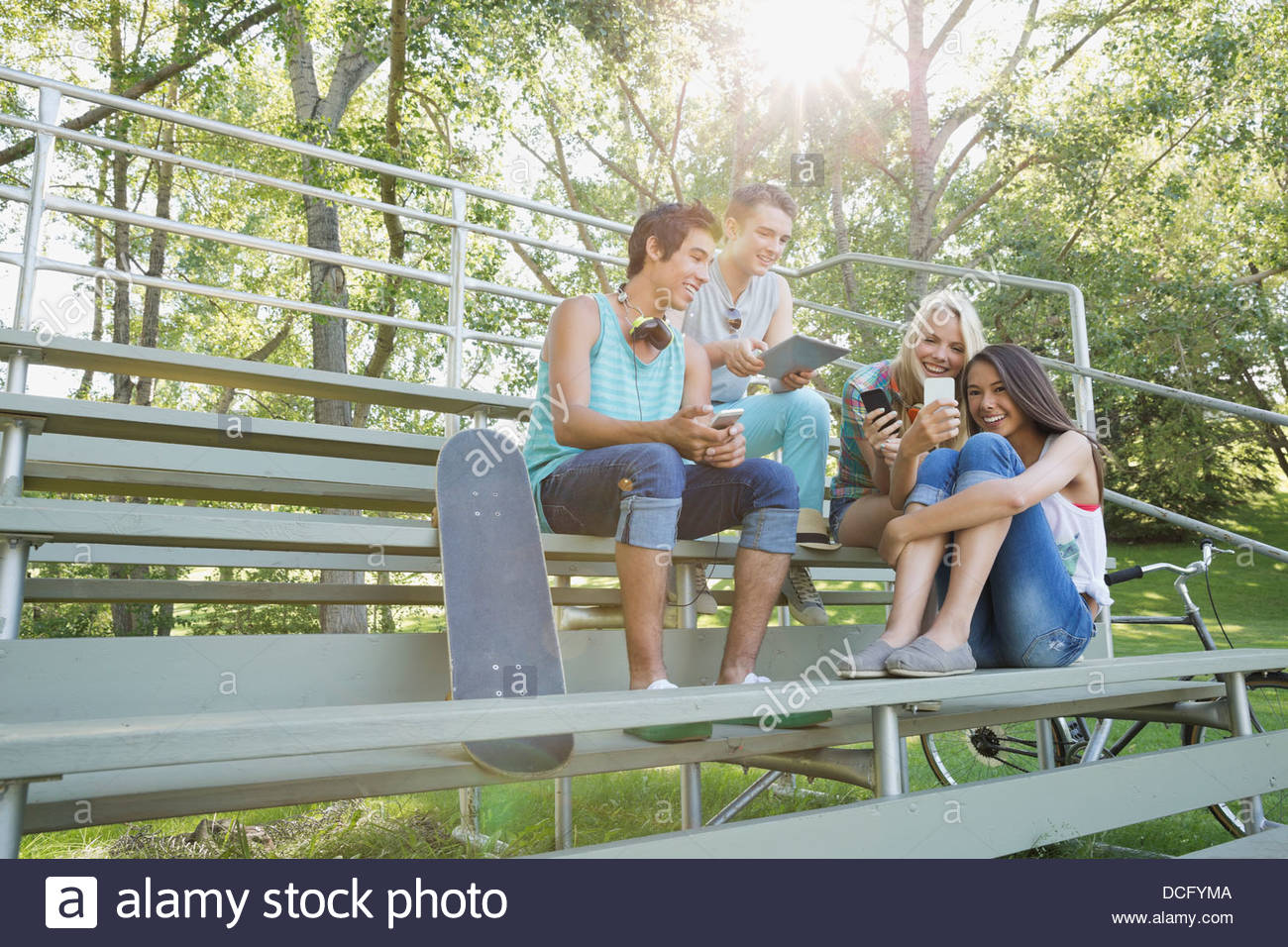 Teens using smart devices outdoors - Stock Image