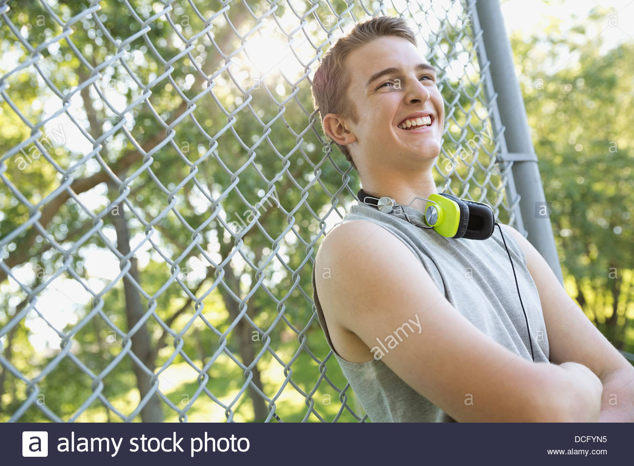 Smiling teen leaning on chain-link fence - Stock Image