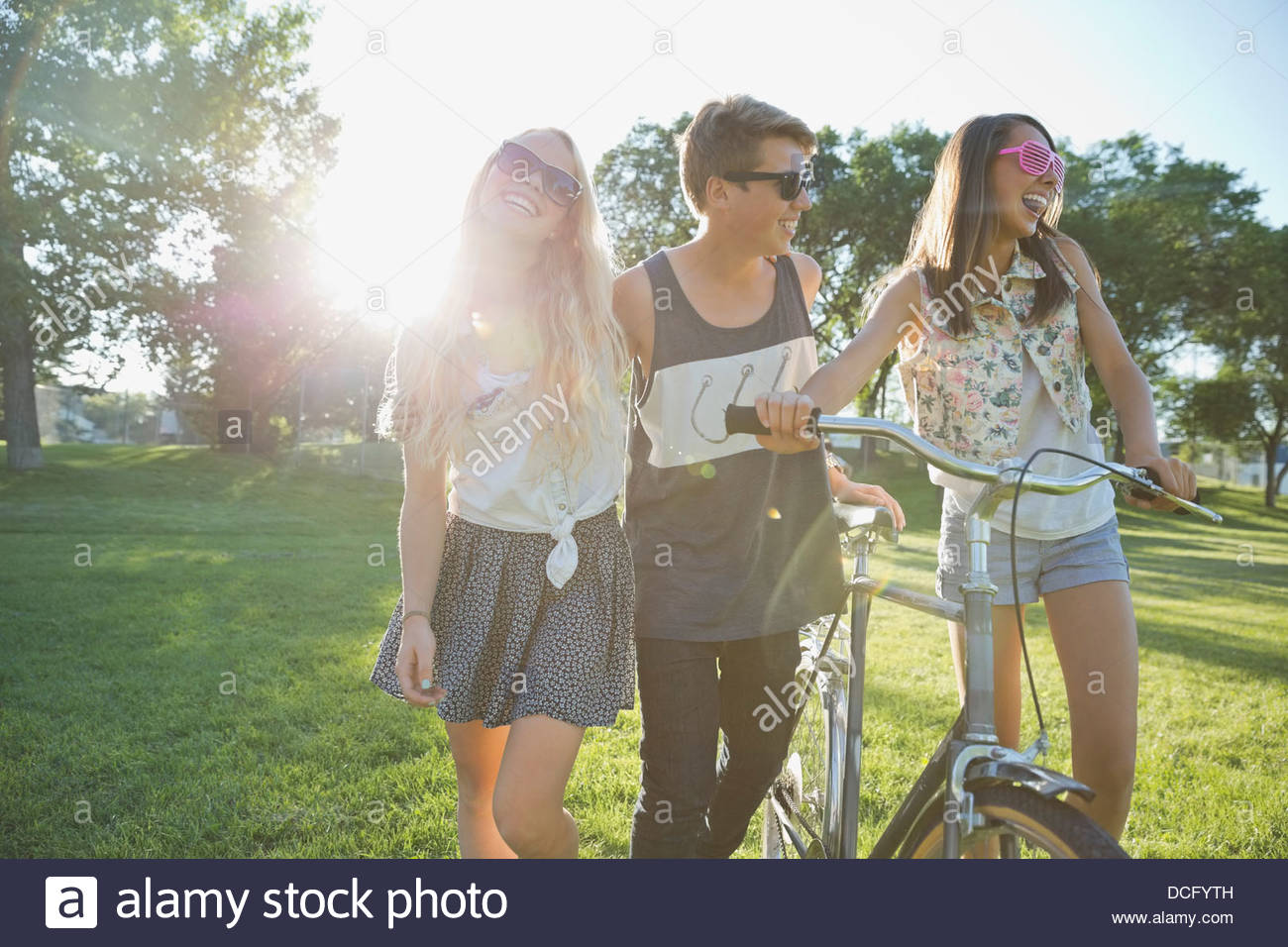 Happy teenage friends with bicycle walking in park - Stock Image