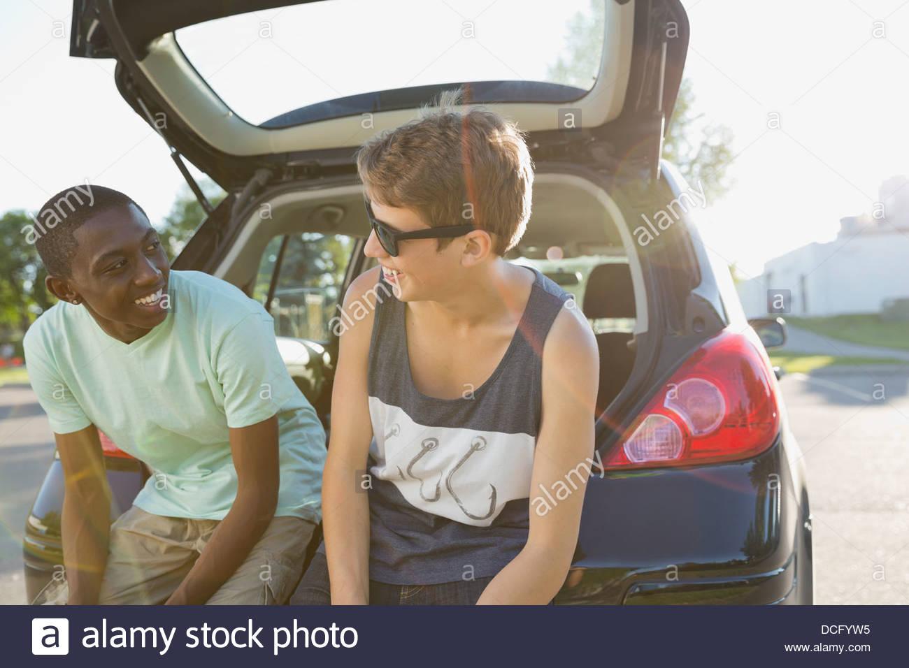 Teens sitting on car bumper - Stock Image