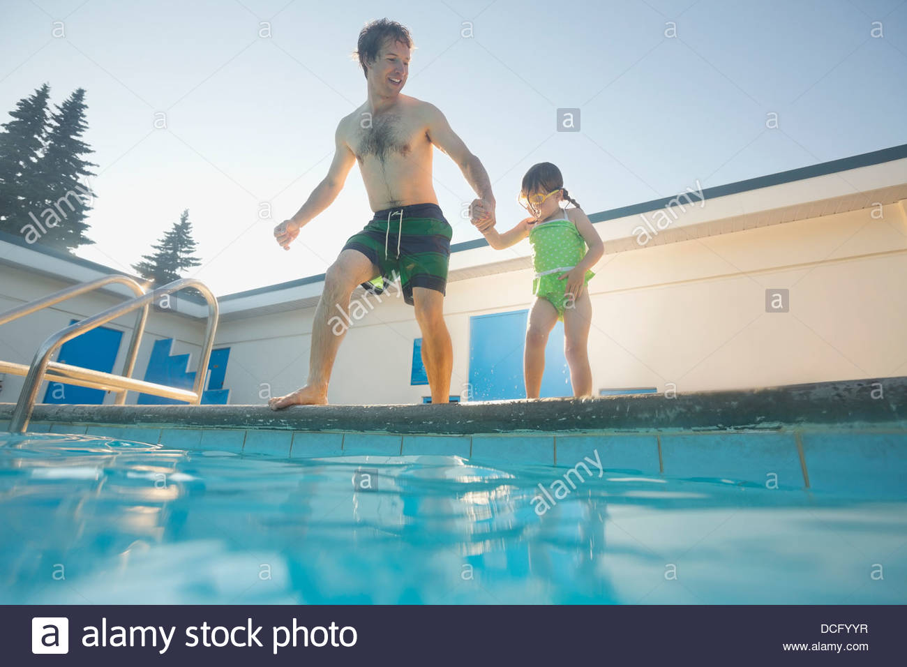Father and daughter preparing to jump into swimming pool - Stock Image