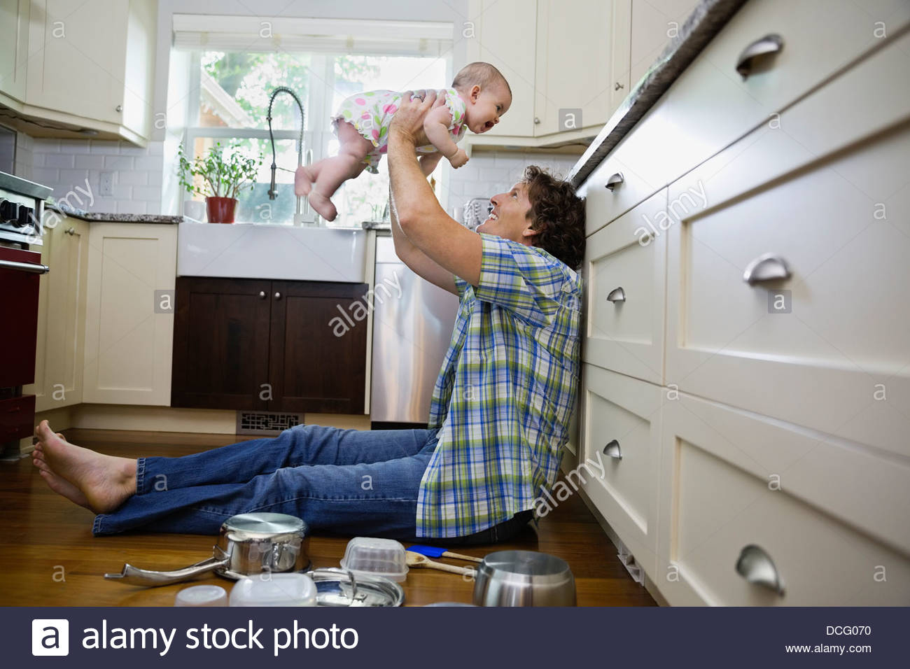 Profile shot of father playing with baby girl in kitchen - Stock Image
