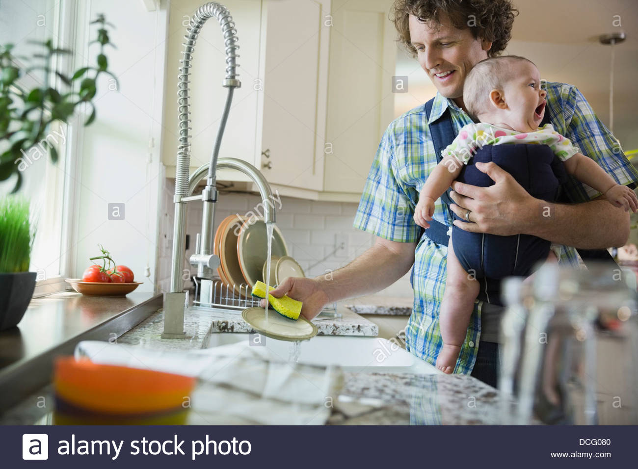 Father washing dishes while carrying baby girl - Stock Image