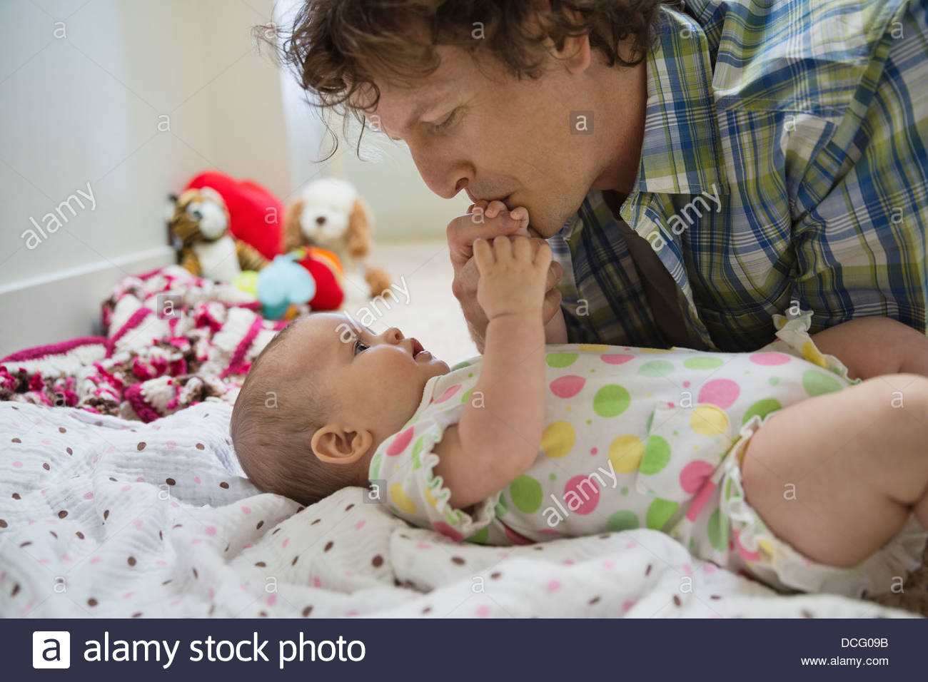 Father kissing baby girls hand - Stock Image