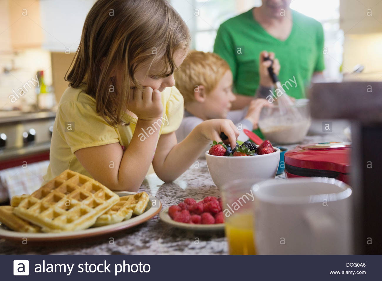 Little girl picking out berries for breakfast - Stock Image