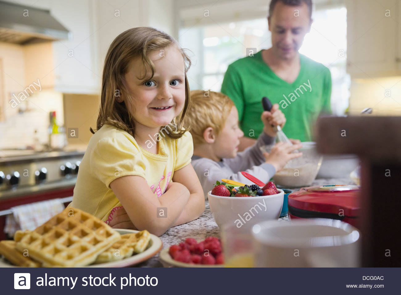 Portrait of girl making breakfast with family - Stock Image