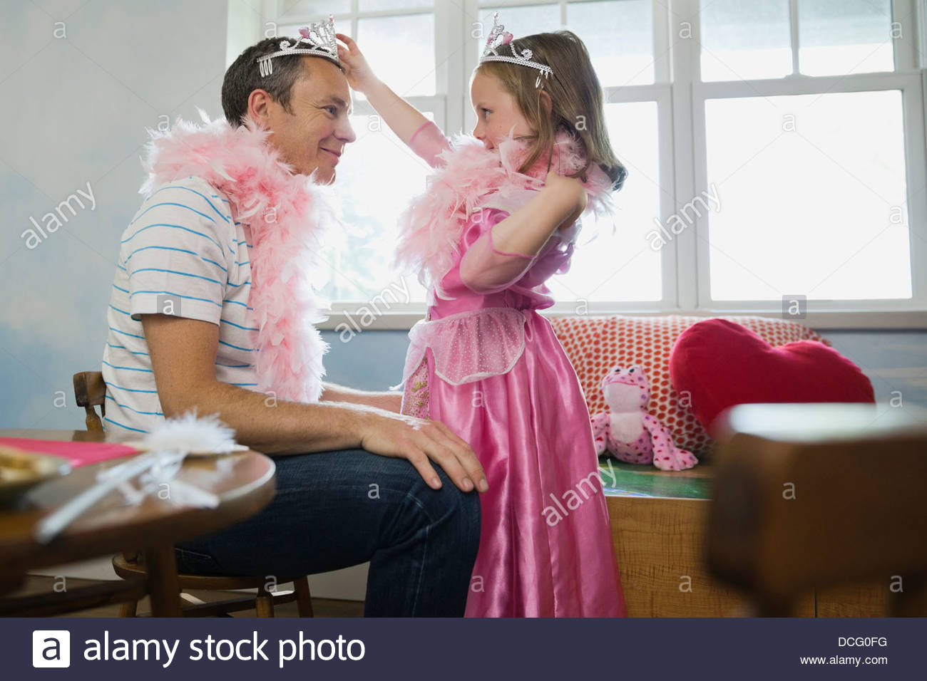 Little girl putting tiara on her dad - Stock Image