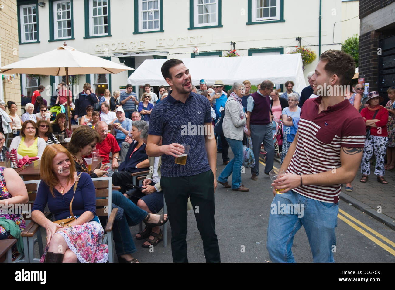 Young men drinking and larking about on the street during Brecon Jazz Festival 2013 - Stock Image