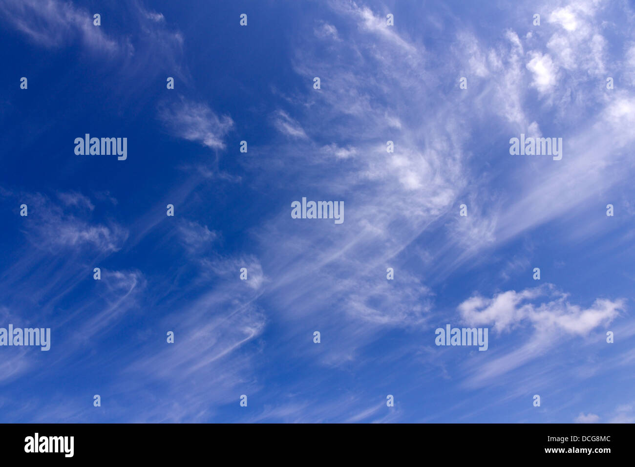 High wispy white cirrus mare's tail clouds against blue sky, UK - Stock Image