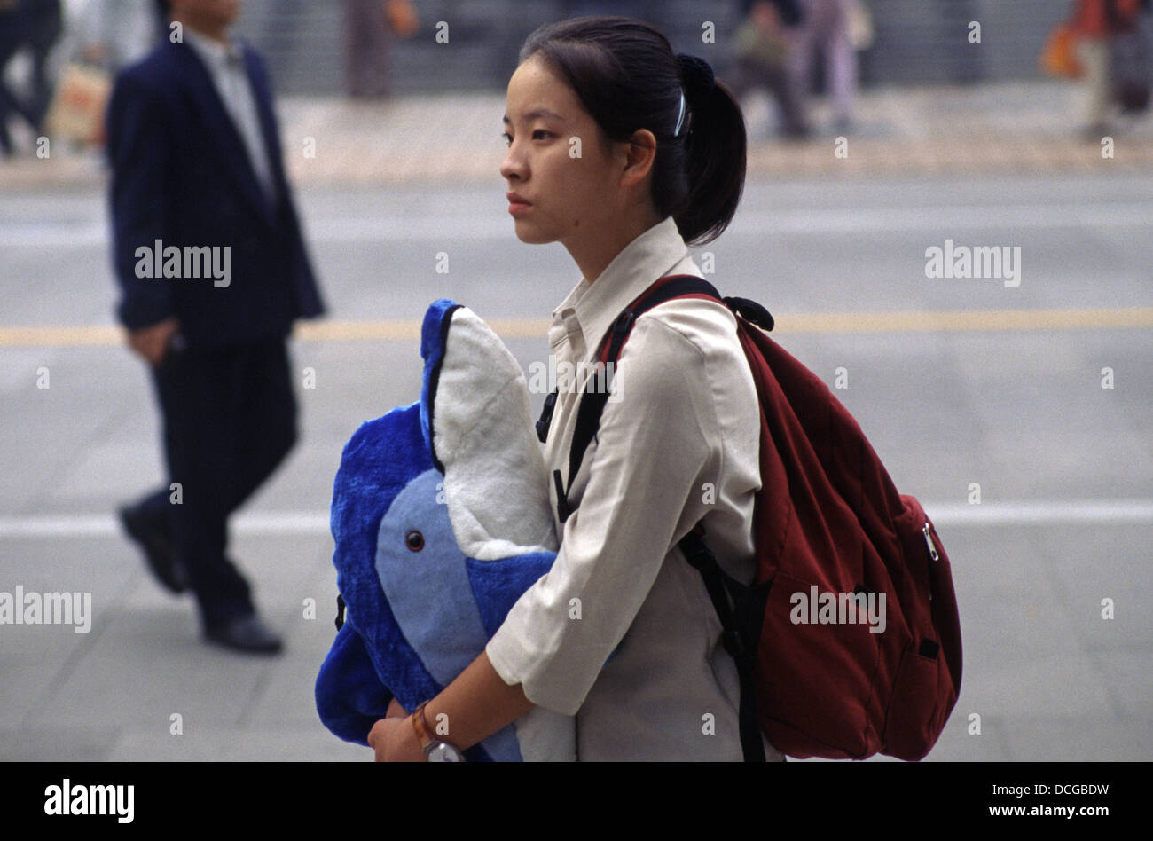 A young Chinese schoolgirl carrying a dolphin toy in Wangfujing pedestrian street located in Dongcheng District - Stock Image