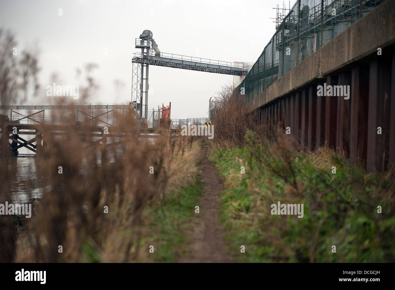 A towpath leads to a commercial ship loading and unloading area on the River Thames - Stock Image
