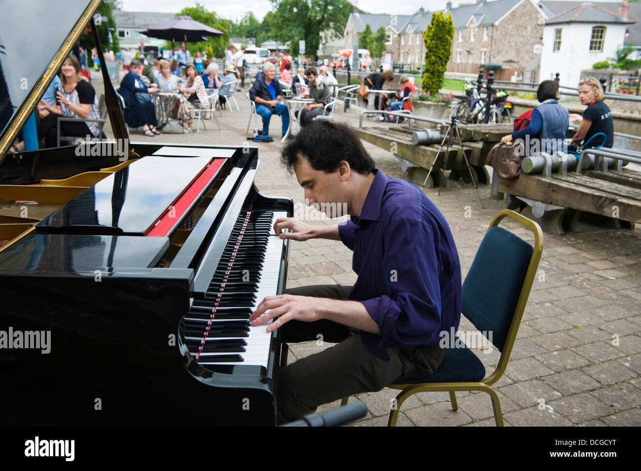 Pianist Sergei playing piano entertaining crowds outside canalside during Brecon Jazz Festival - Stock Image