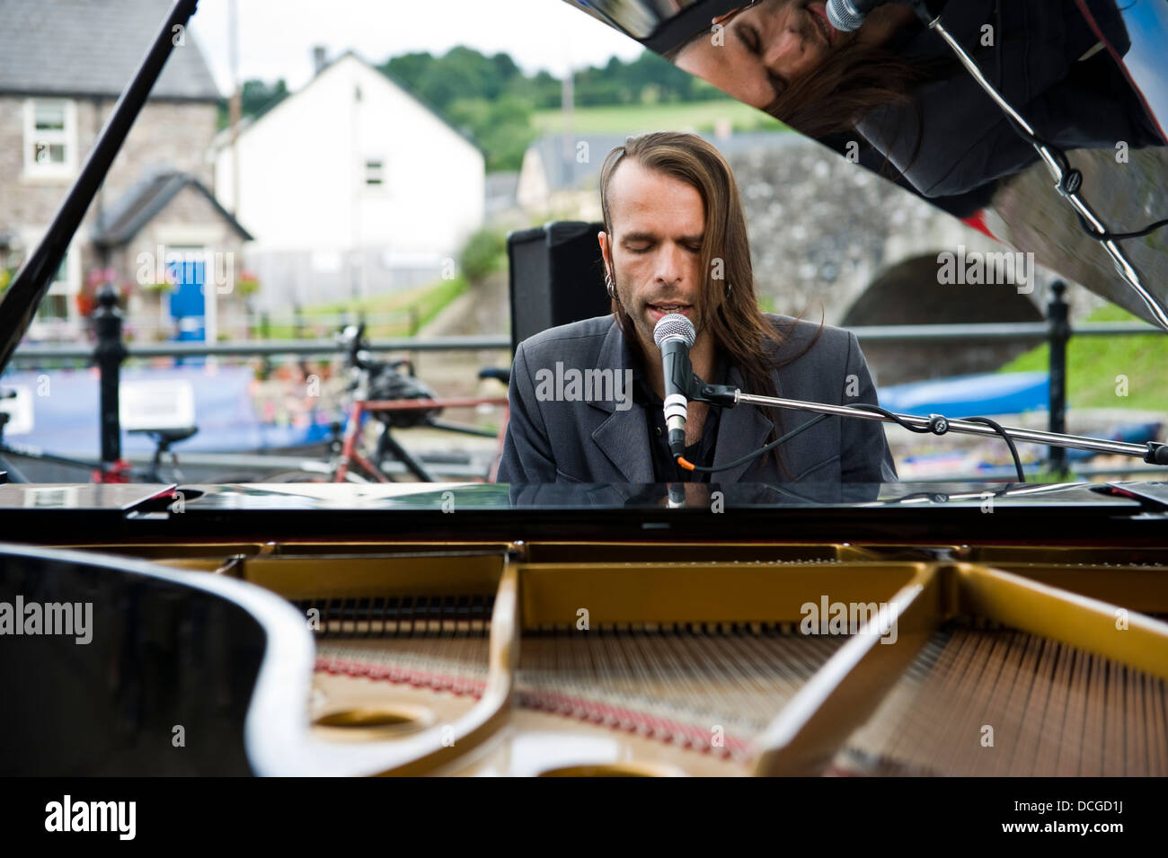 Pianist Ten Sheds playing piano entertaining crowds outside canalside during Brecon Jazz Festival - Stock Image