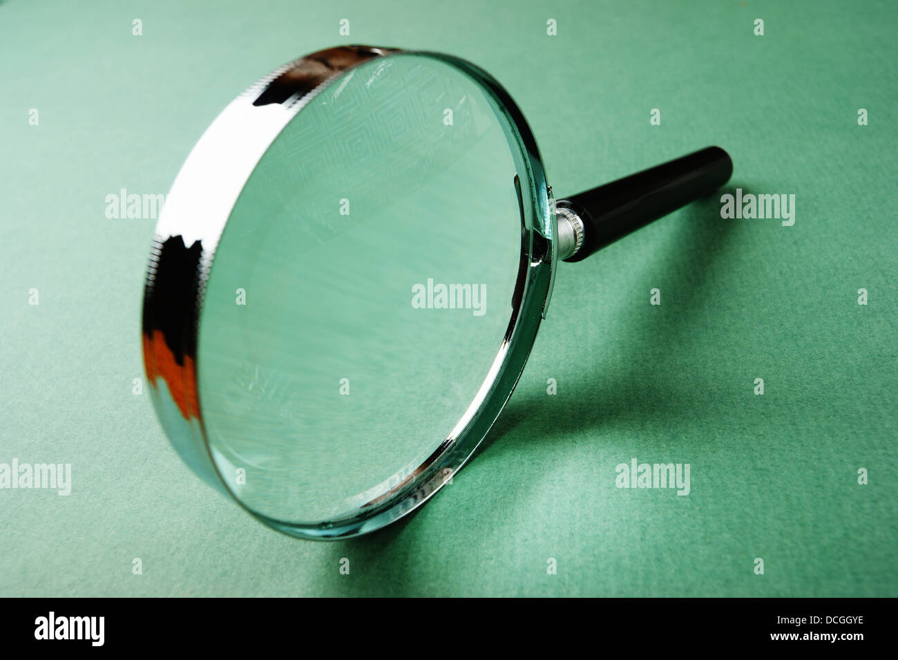magnifying glass on green background - Stock Image