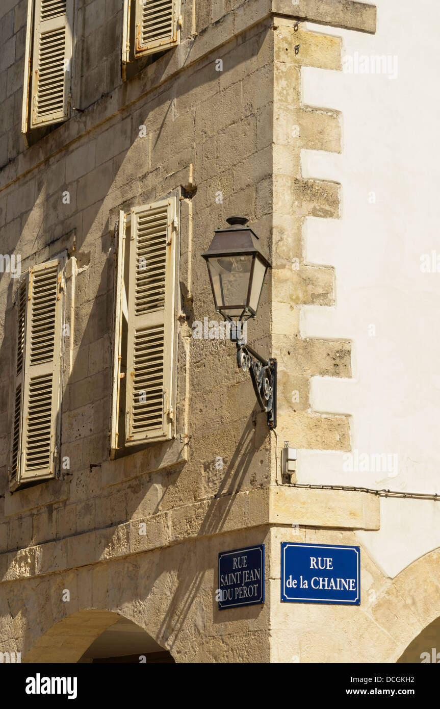 Shuttered windows and old wall mounted lamp post La Rochelle Charente Maritime France - Stock Image