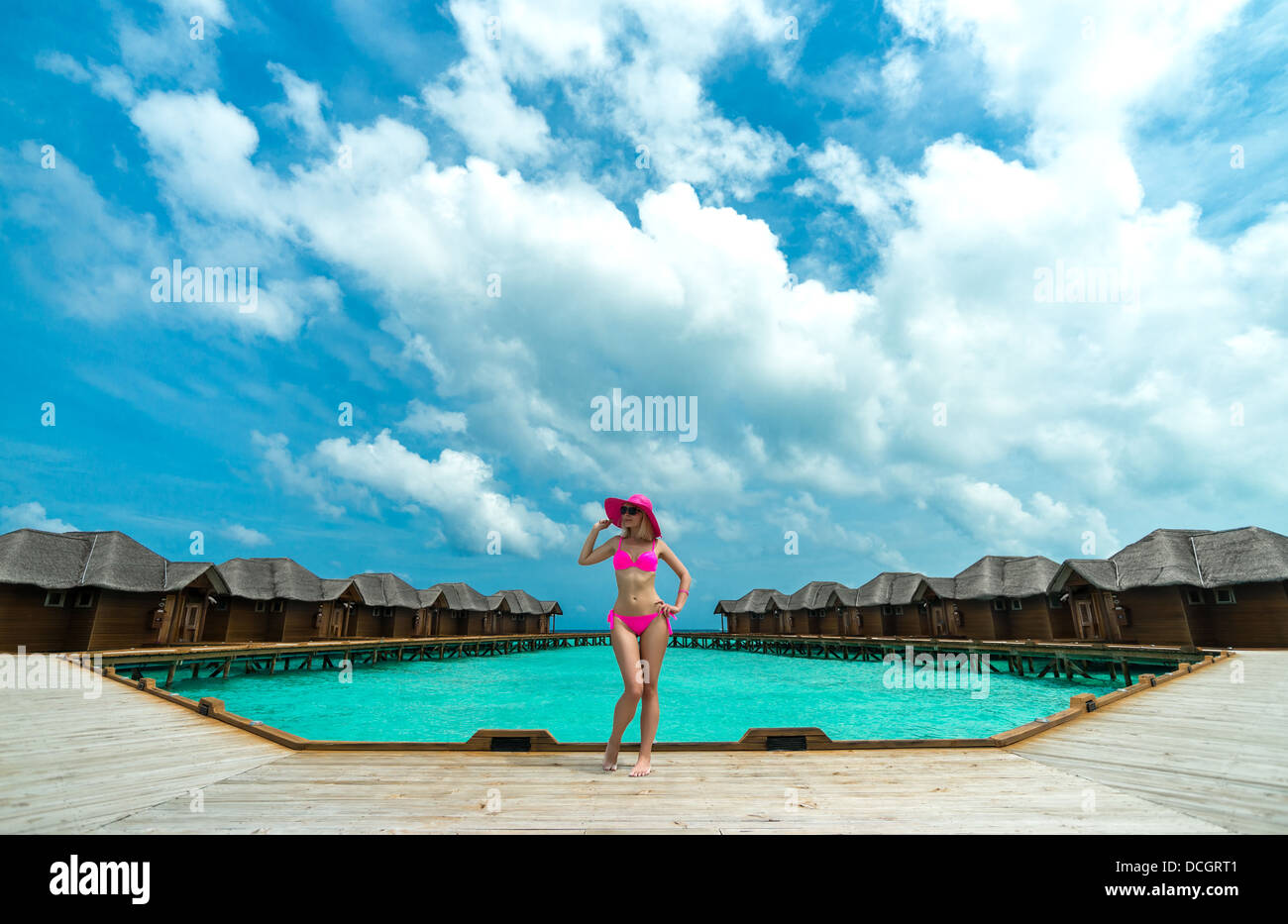 Woman on a beach jetty at Maldives - Stock Image