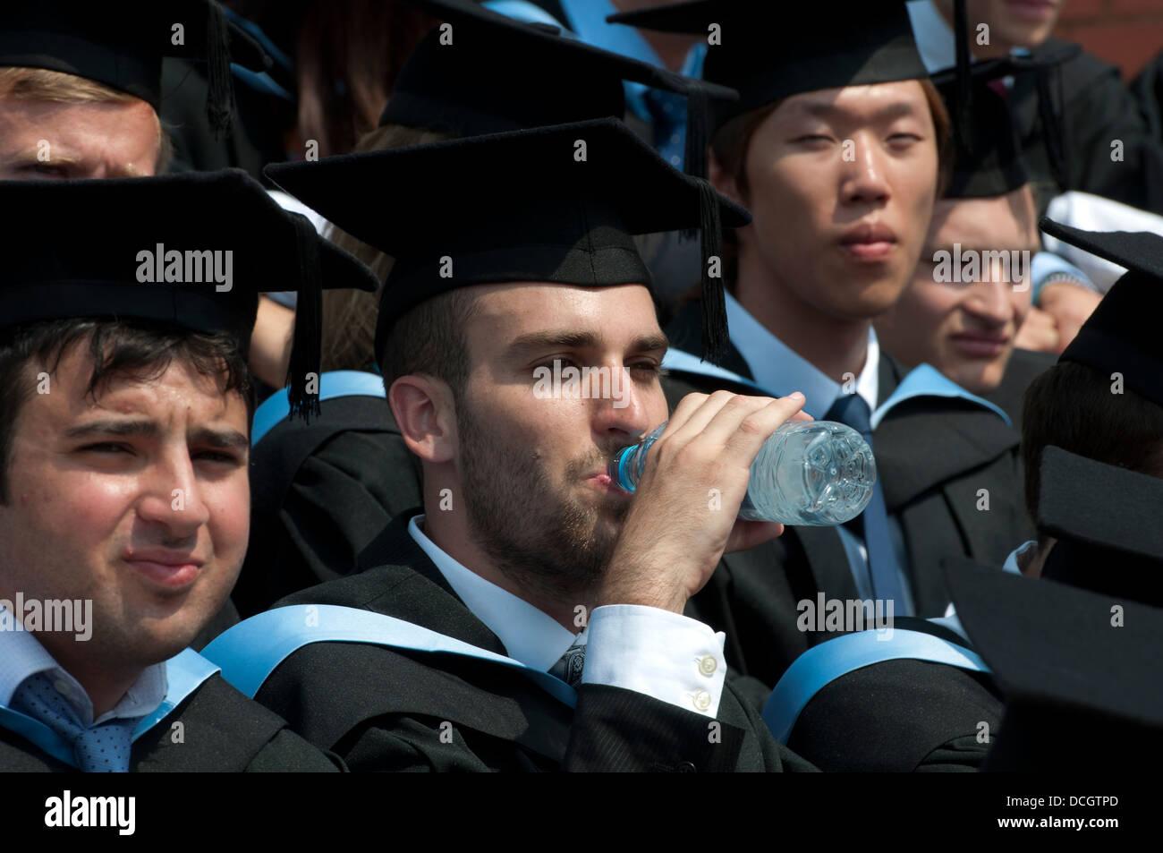 Warwick University graduation day. A graduate drinking water. - Stock Image