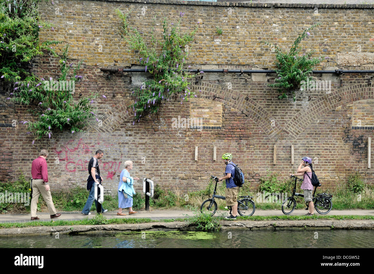 Leisure cyclists giving way to pedestrians or walkers on the Regent's Canal towpath, London Borough of Camden, - Stock Image