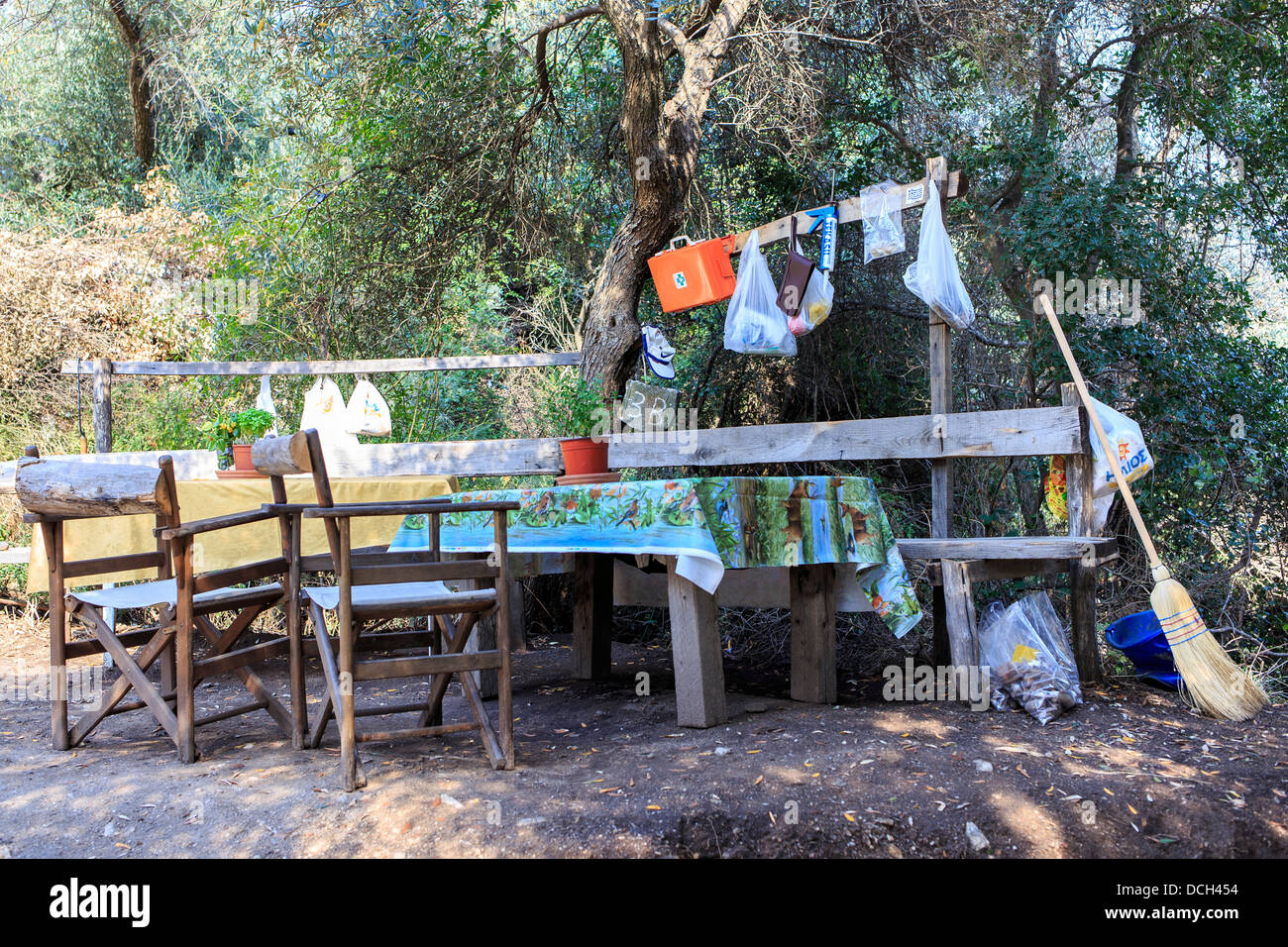Wooden chairs, desk, broom, olive tree in the background and a first aid kit. - Stock Image