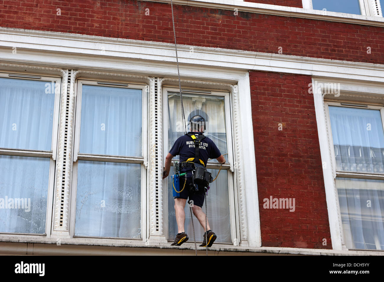 window cleaner using abseil rope London England UK Stock Photo