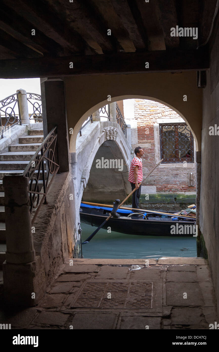 A Venetian oarsman standing up rowing his gondola after ducking a surbased bridge (Venice - Italy). - Stock Image