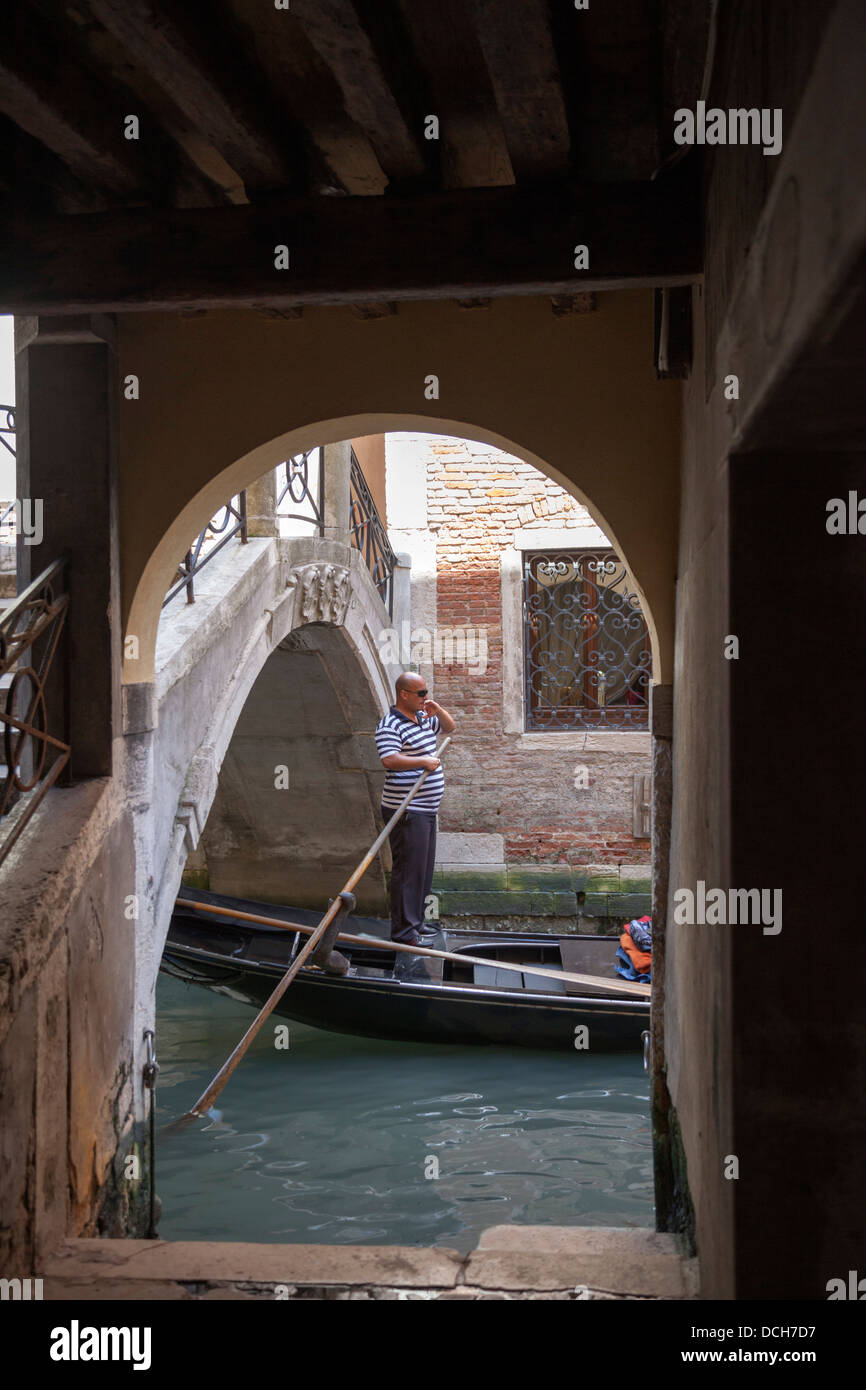 A Venetian oarsman standing up rowing his gondola after ducking a vaulted bridge (Venice - Italy). Gondolier pilotant - Stock Image