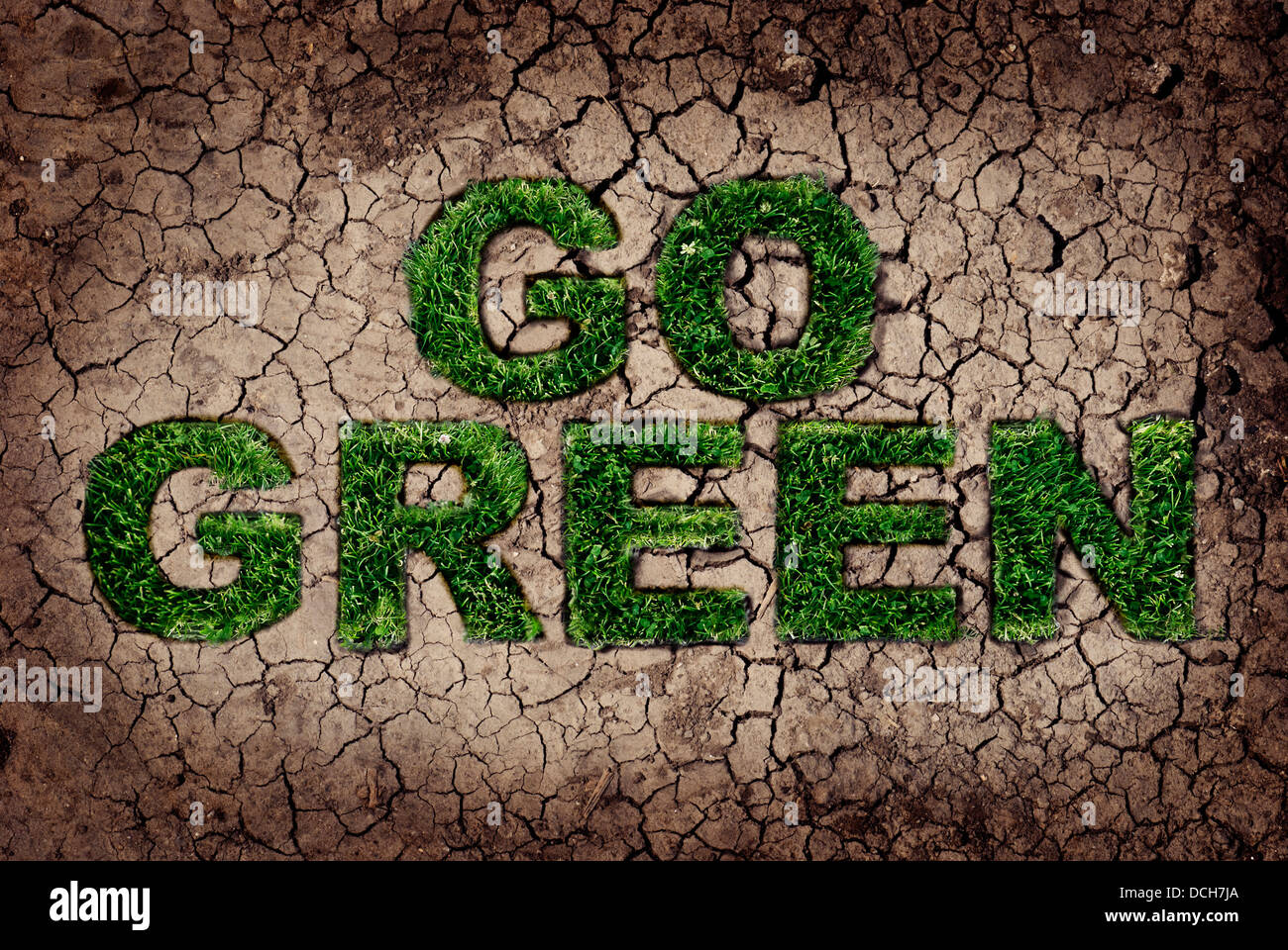 Eco concept. Grass growing from dry soil in Go Green shape. Stock Photo