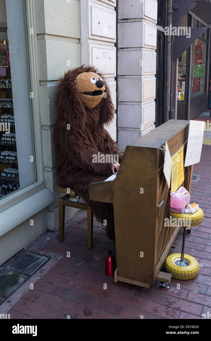 A person in fancy dress (as Ralph from the Muppets) plays piano on a street - Stock Image