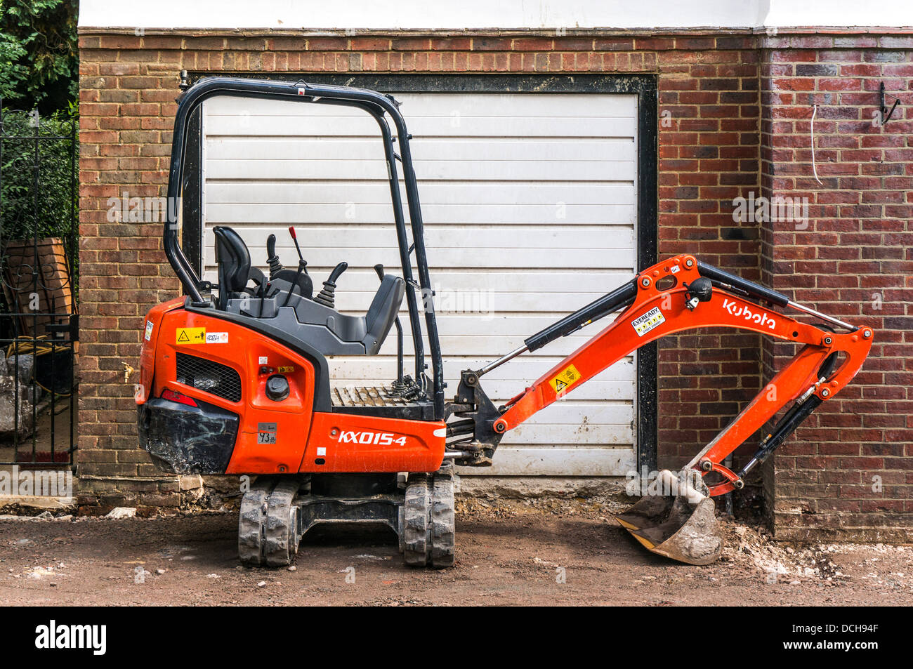 A hydraulic digger, parked outside a garage, used to prepare the ground for a new driveway at a house in Banstead, - Stock Image