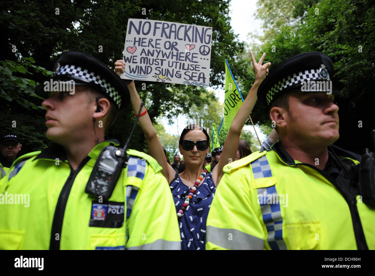 Balcombe, West Sussex, UK. 18th August 2013.  A young woman holds up a poster behind police line as thousands of protesters converged on Balcombe in West Sussex today to march and protest against the Cuadrilla fracking site in the village .  Photograph taken by Simon Dack/Alamy Live News Stock Photo