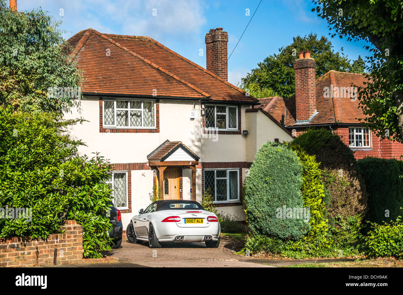 An upmarket period detached house with car parked outside, in Surrey, England, UK. Stock Photo