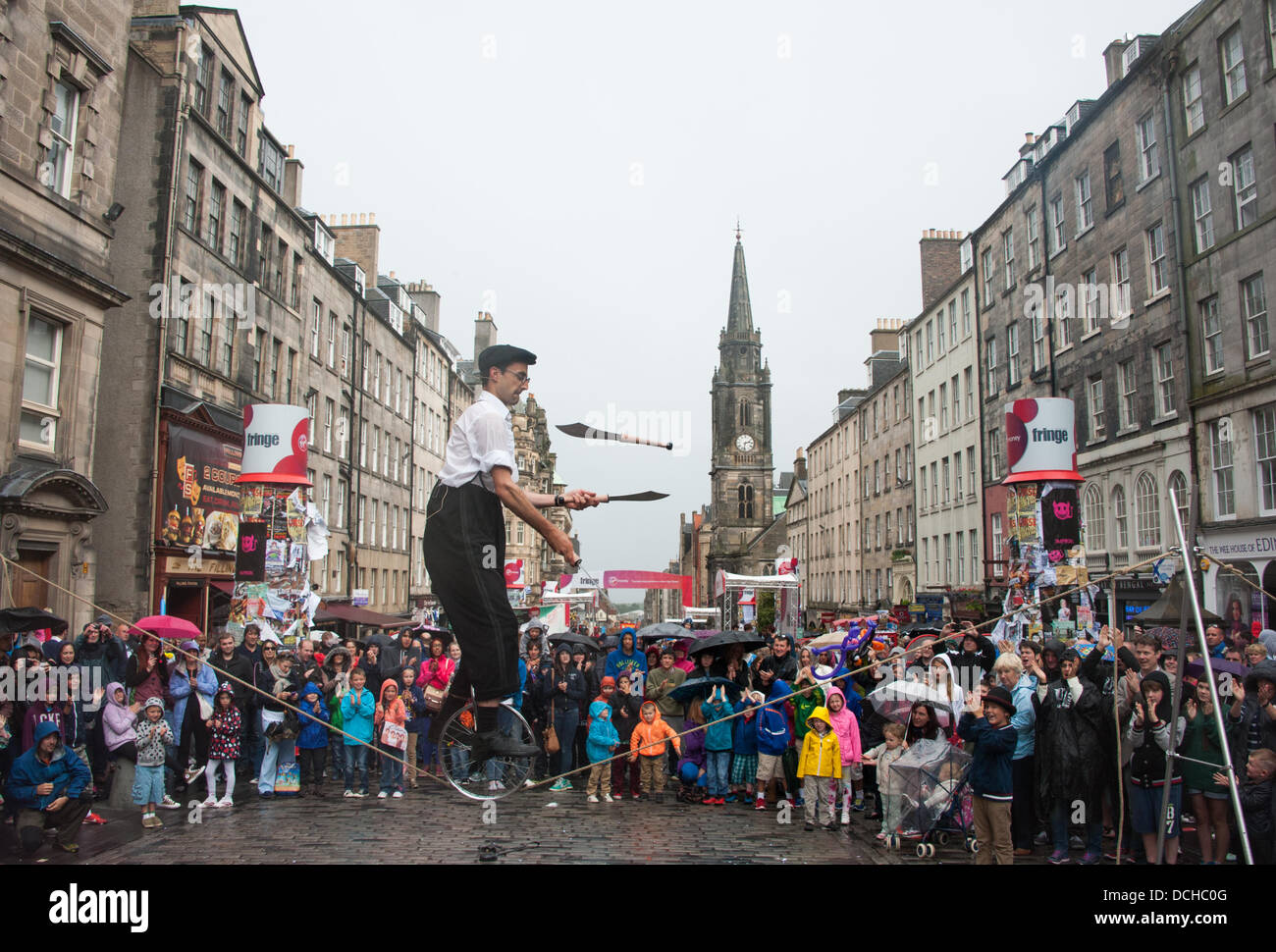 Edinburgh, UK. 18th Aug, 2013. A uni cycling Frenchman on a tight rope juggles daggers in the rain on the Royal - Stock Image