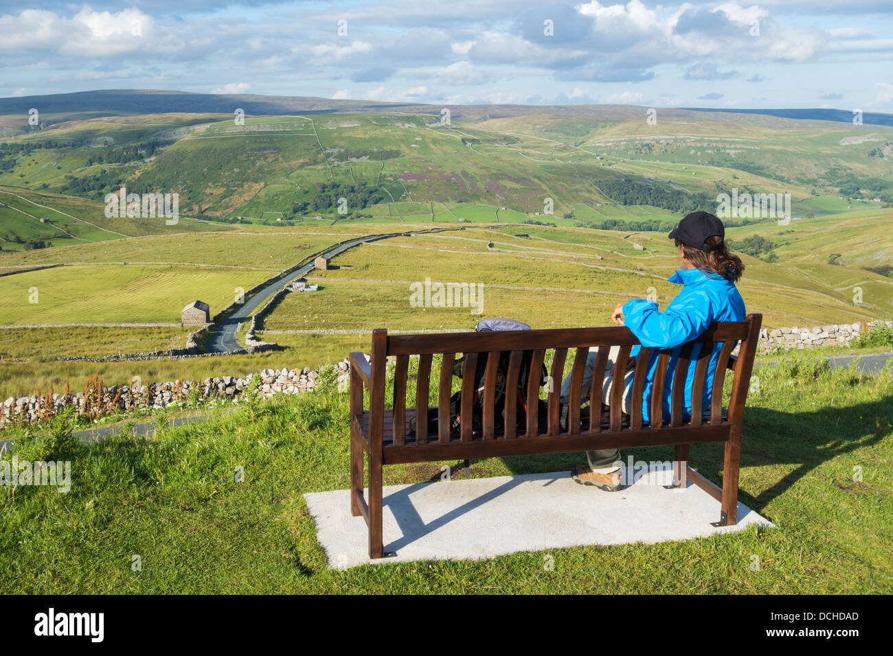 Female hiker on seat overlooking Buttertubs pass in The Yorkshire Dales National Park. Yorkshire, England, UK - Stock Image