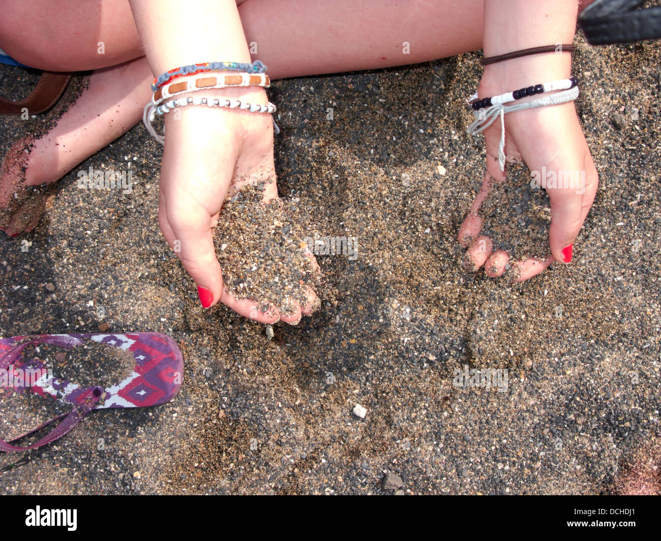 teenage girl letting Sand slipping through fingers - Stock Image
