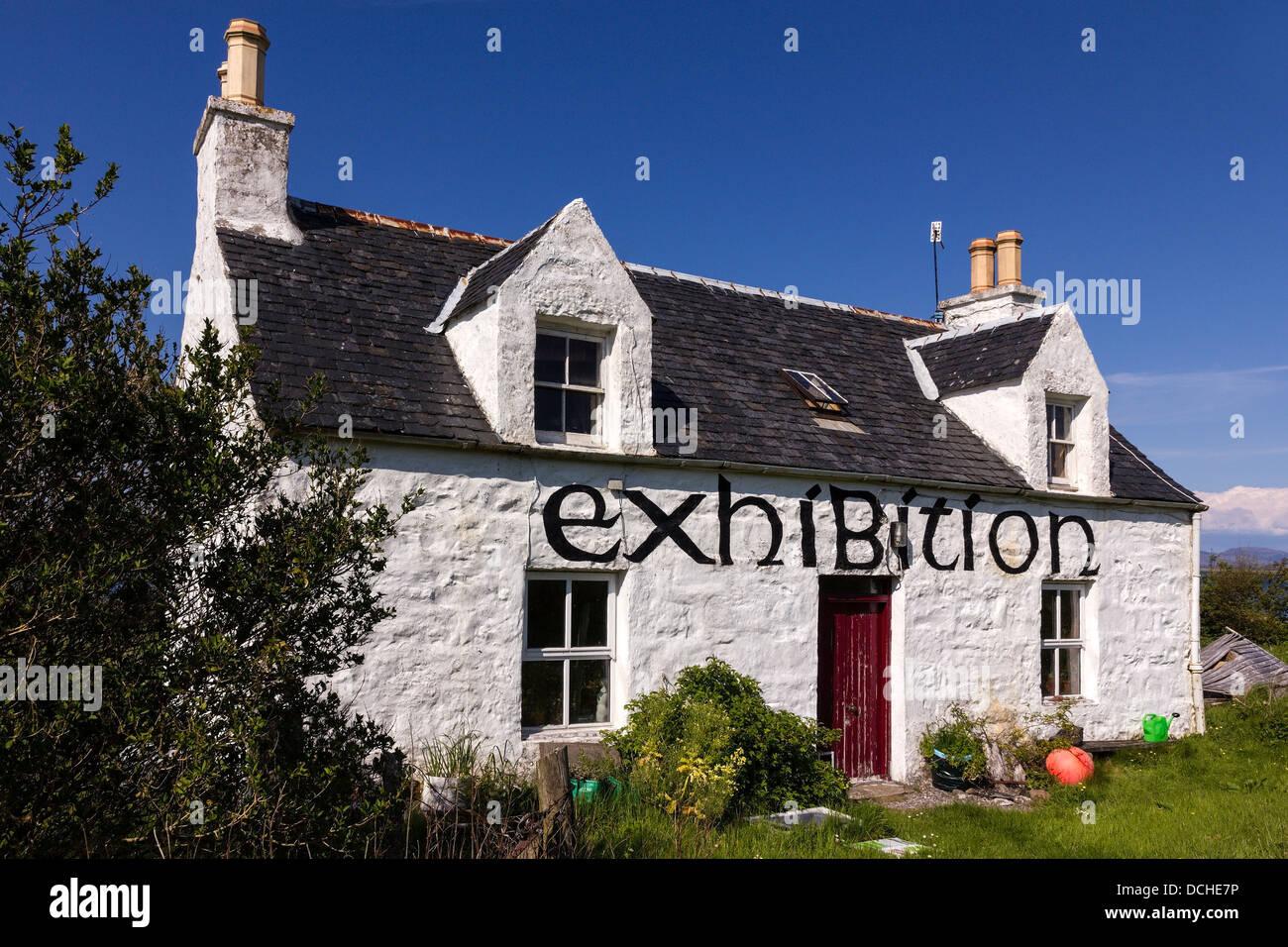 Old white painted 'exhibition' croft cottage against blue sky, Broadford, Isle of Skye, Scotland, UK - Stock Image