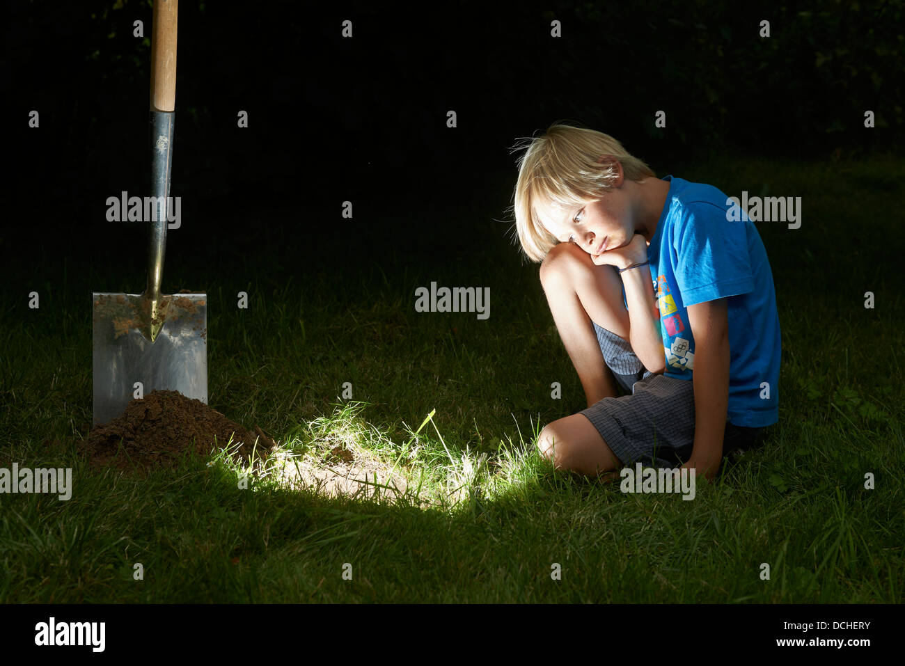 Child boy digging a treasure in magic hole in soil at dusk