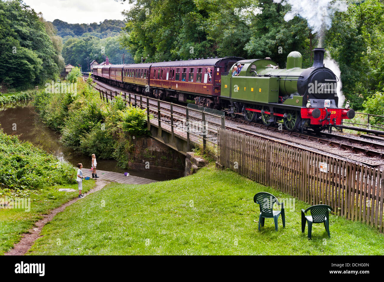 A steam train leaves Consall Station and crosses the Caldon Canal on the Churnet Valley Railway, Leek, Staffordshire, - Stock Image