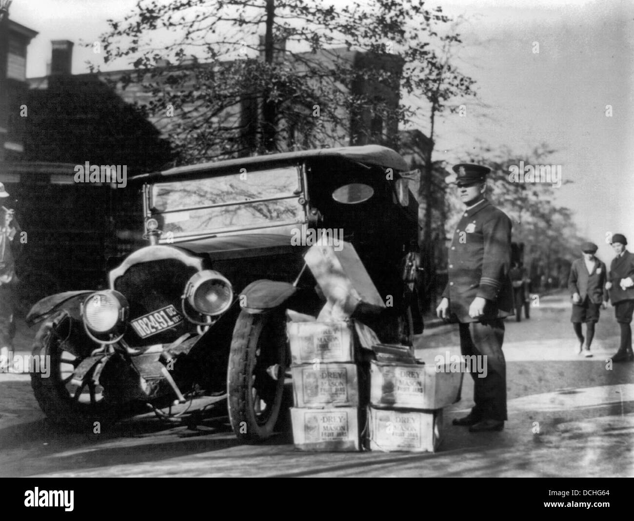 Policeman standing alongside wrecked car and cases of moonshine, during USA Prohibition circa 1922 - Stock Image