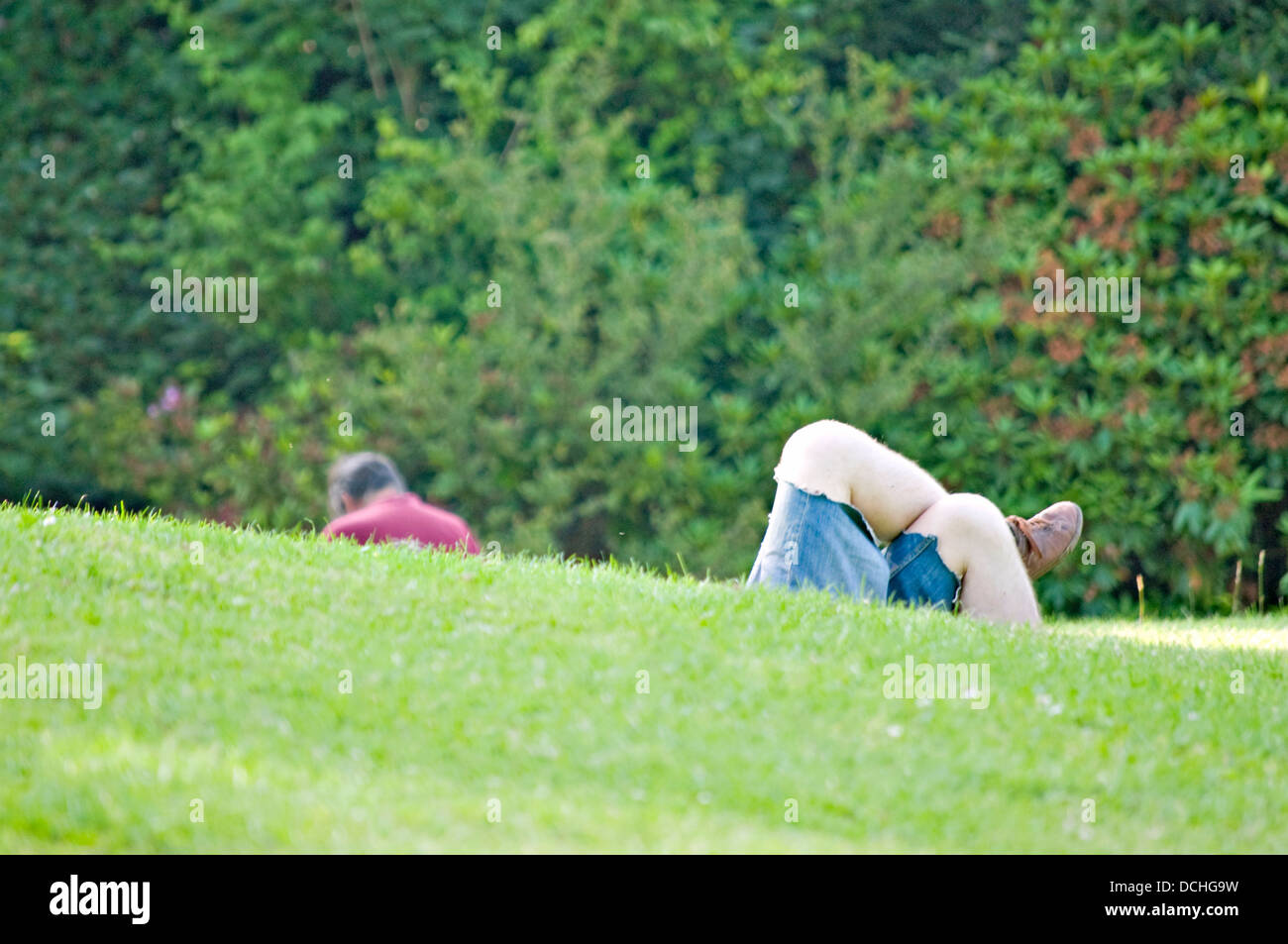 UK park scene, with someone's back, and a pair of crossed legs appearing from behind a grass slope. - Stock Image
