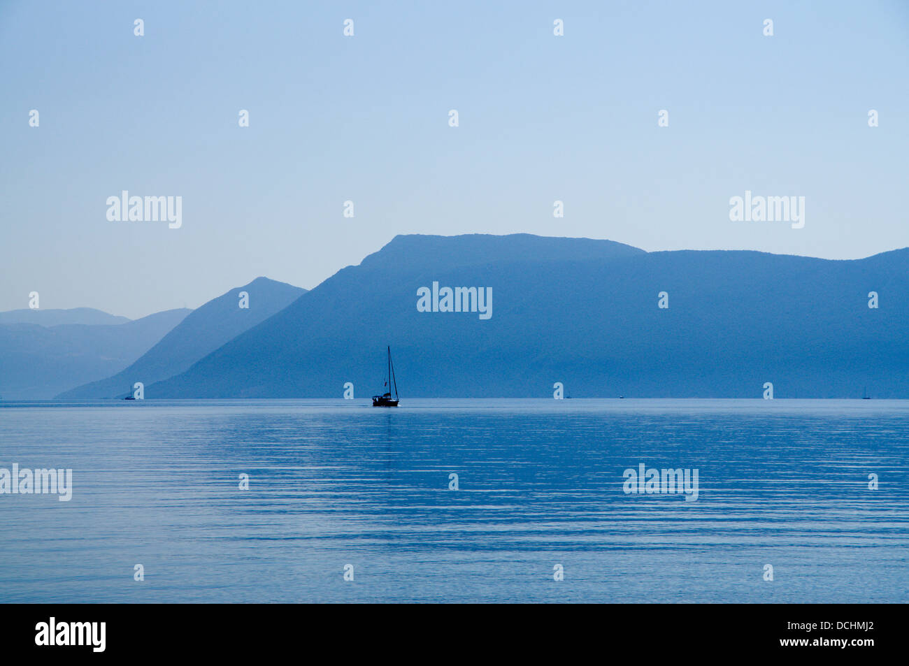 Yacht  off Meganisi Island with the mountains of  mainland greece and Kalamos Island in the distance, Ionian Islands,Greece. - Stock Image