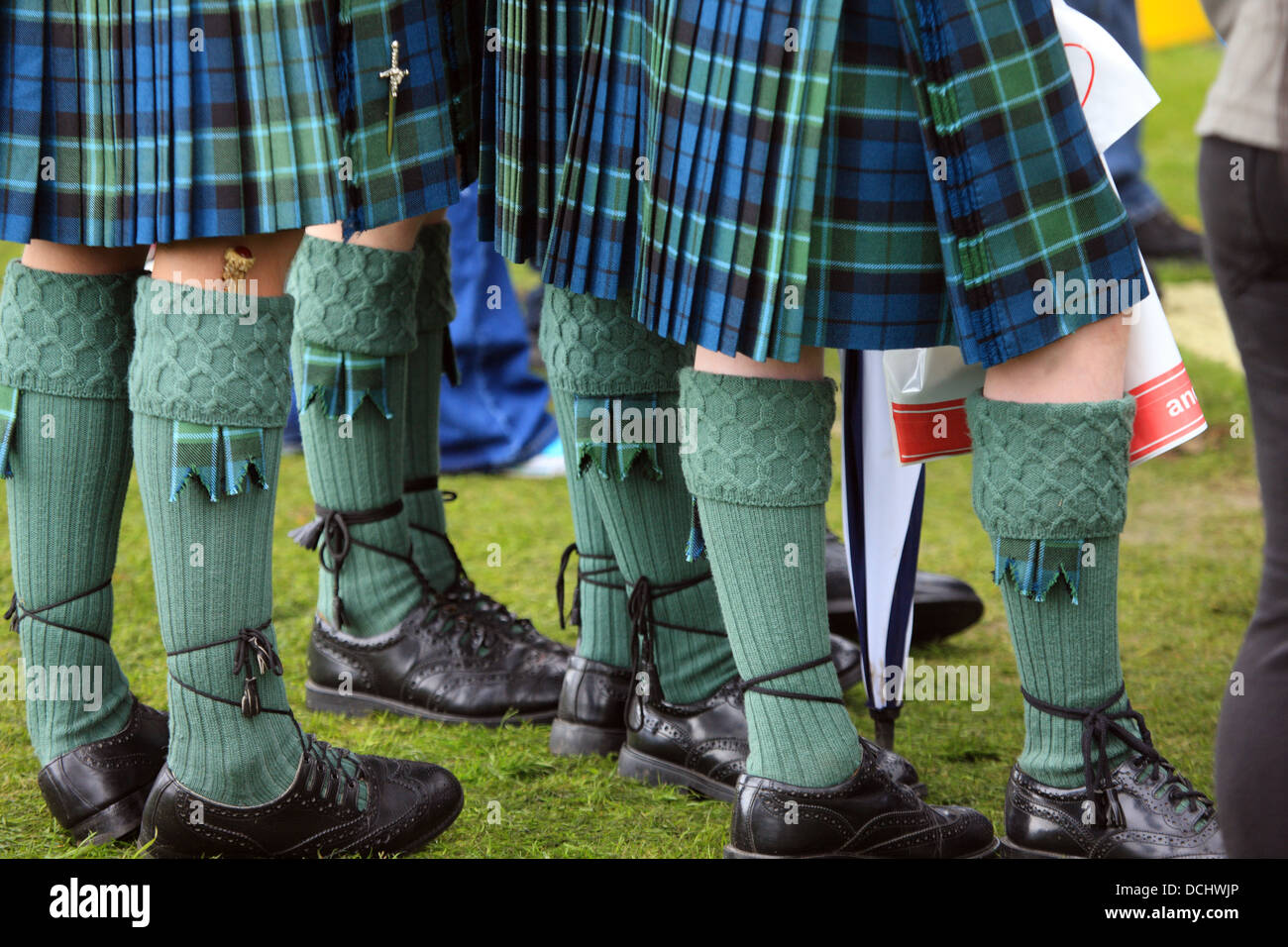 Scottish national dress - tartan kilts, highland dress shoes, socks with flashes at the World Pipe Band Championships - Stock Image