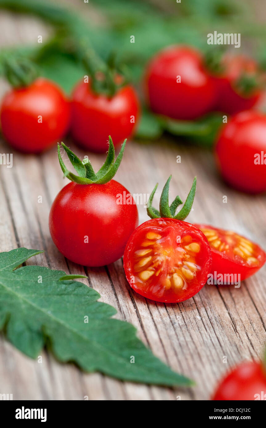 Cherry tomatoes on wooden surface - Stock Image