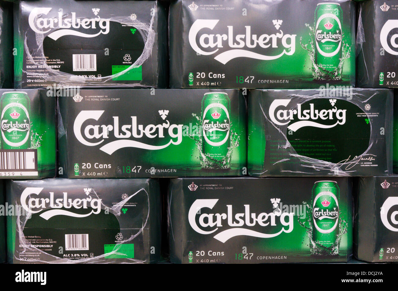 Boxes of Carlsberg beer cans stacked in a supermarket. - Stock Image