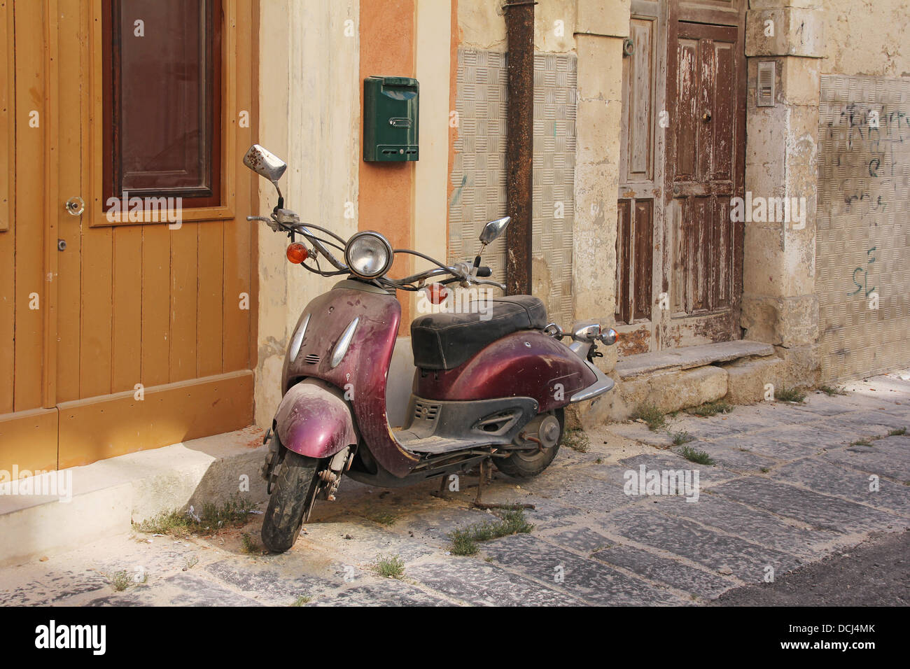 Old rusty purple scooter oldtimer motorcycle left in an abandoned street - Stock Image