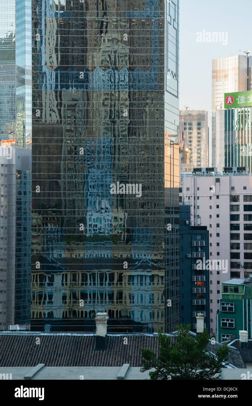 A view of Central in Hong Kong with the old prison reflected in a glass buildingin on Hollywood road. - Stock Image