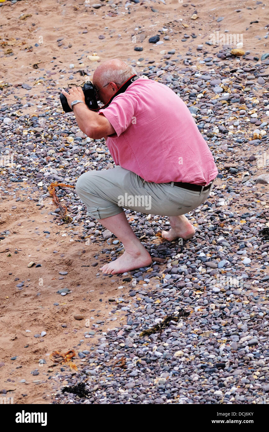 Middle aged man crouching barefoot on a beach taking photos with a camera Stock Photo