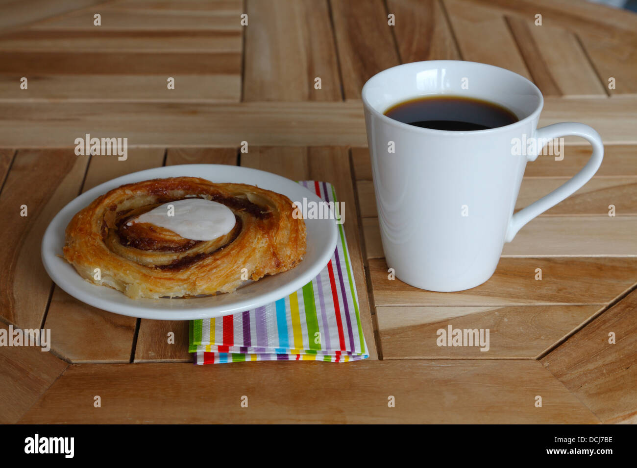 Original Danish pastry of laminated yeast-leavened dough - flaky and delicate crust and a mug of coffee on a café - Stock Image