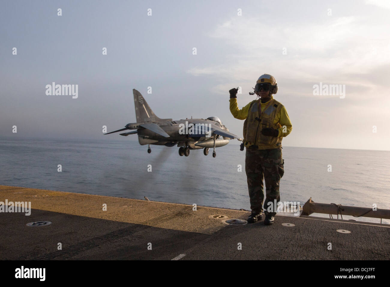 Aviation Boatswain's Mate (Handling) Airman Lucy Pizarro signals as an AV-8B Harrier takes off from the amphibious - Stock Image