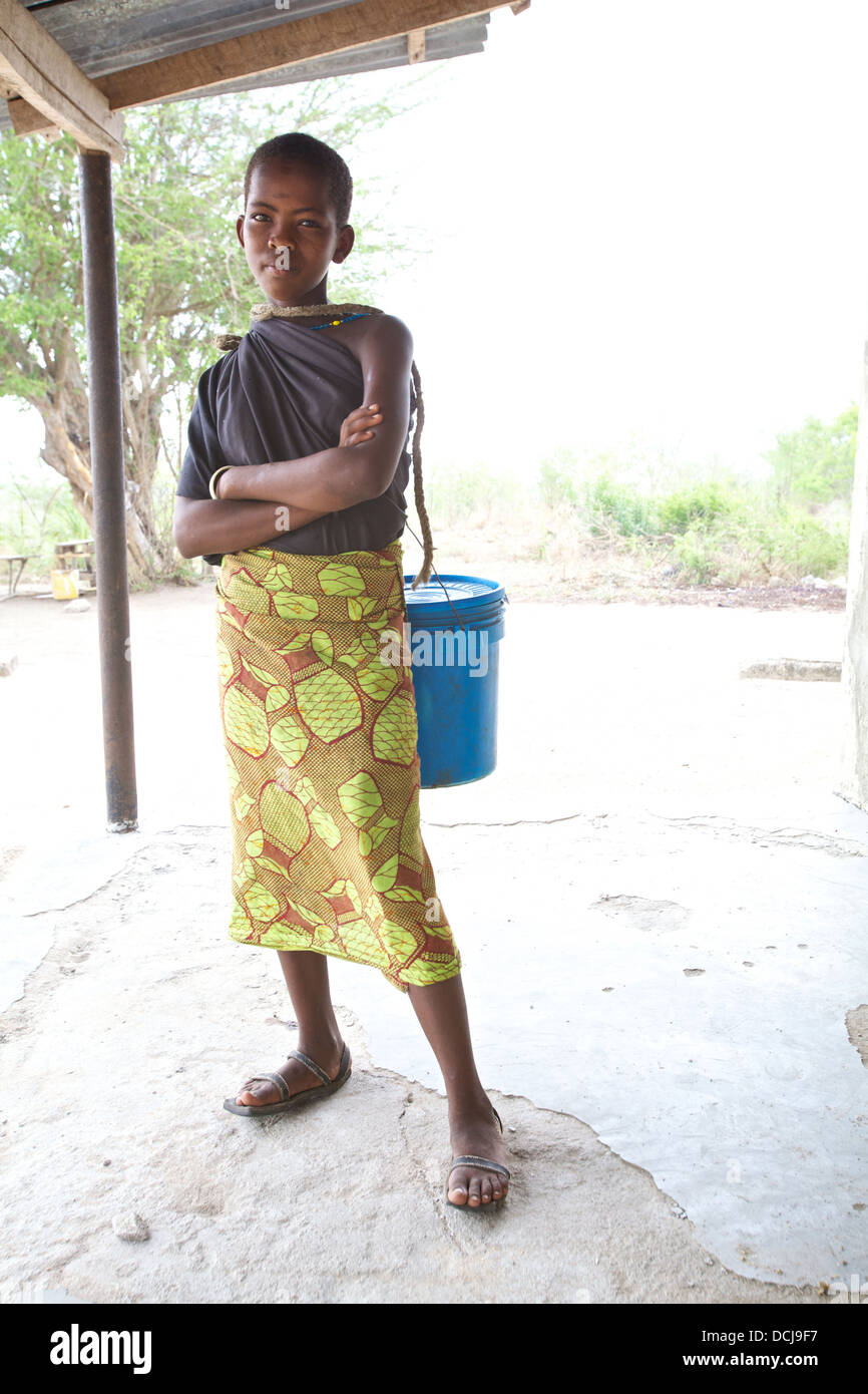 Young Tanzanian girl with bucket for carrying water, Miono Region, Tanzania - Stock Image