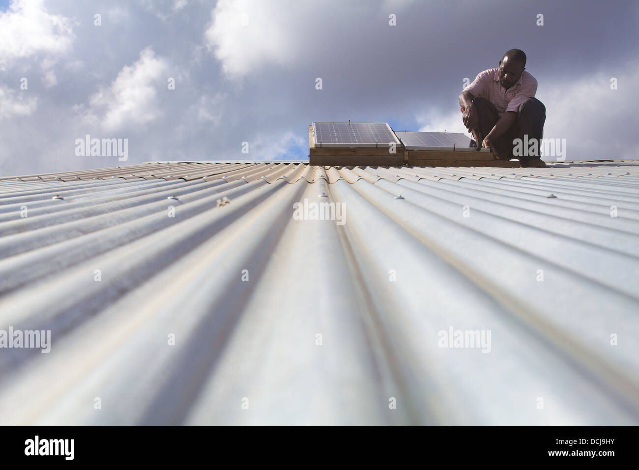 Solar panel technician carrying out maintenance work on a corrugated roof, Miono Region, Tanzania. - Stock Image